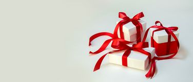 Christmas Gift`s in White Box with Red Ribbon on Light Background. New Year Holiday Composition Banner. Copy Space For Your Text Royalty Free Stock Photos