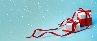 Christmas Gift`s in White Box with Red Ribbon on Light Blue Background. New Year Holiday Composition Banner. Copy Space Stock Photo
