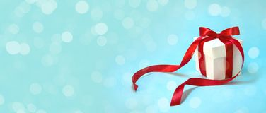 Christmas Gift`s in White Box with Red Ribbon on Light Blue Background. New Year Holiday Composition Banner. Copy Space royalty free stock photo
