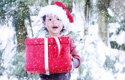 Christmas gift by santa girl in winter snow Royalty Free Stock Photo