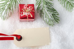Christmas Gift on Snow with Tag Stock Photography