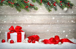 Christmas gift in snow, wood background Stock Photos