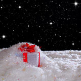 Christmas gift in a snowdrift under the starry sky Stock Photo