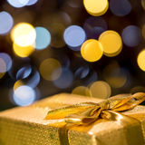 Christmas gift with sparkling lights background. Wrapped in gold paper Royalty Free Stock Photo
