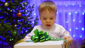 Christmas gift surprise - A kid opens present. In the background, bokeh lights and garlands. stock footage