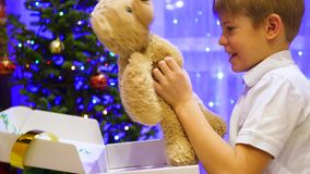 Christmas gift surprise - A kid opens present teddy bear. In the background, bokeh lights and garlands. stock video footage