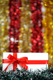 Christmas gift among a tinsel Royalty Free Stock Images