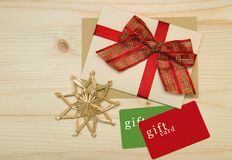 Christmas gift. Top view of christmas present. Gift cards, postcard with red ribbon bow, handmade snowflake on a wooden background royalty free stock photos