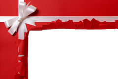 Christmas gift torn open revealing copy space inside, white ribbon bow, red wrapping paper background Royalty Free Stock Photo