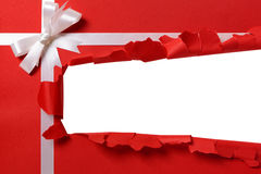 Christmas gift torn open strip, white ribbon bow, red wrapping paper. Background, copy space Stock Photos