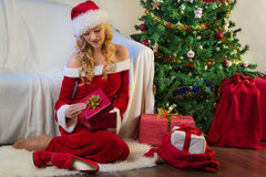 Christmas gift, tree and beautiful young woman Royalty Free Stock Images