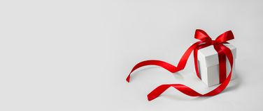Christmas Gift in White Box with Red Ribbon on Light Background. Minimal New Year Holiday Composition Banner. Copy Space stock photography
