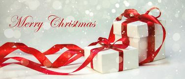 Christmas gift in white box with red ribbon on light background. New year holiday composition. Banner Royalty Free Stock Photography