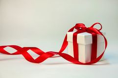 Christmas Gift in White Box with Red Ribbon on Light Background. New Year Holiday Composition. Copy Space Stock Image