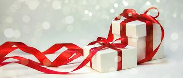 Christmas Gift in White Box with Red Ribbon on Light Background. New Year Holiday Composition. Copy Space Royalty Free Stock Photo