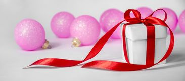 Christmas Gift in White Box with Red Ribbon and Pink Balls on Light Background. New Year Holiday Composition Banner. stock photos