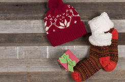 Christmas gift with winter clothes cap and socks. Christmas present and winter knitted cap and socks on wooden background Royalty Free Stock Photo