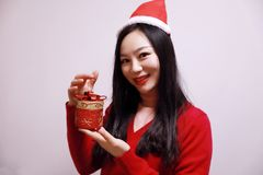 Christmas gift woman. Chinese traditional dress cheongsam holding present isolated on white background. girl in winter sweater showing gift wearing Santa hat Royalty Free Stock Photos