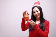 Christmas gift woman. Chinese traditional dress cheongsam holding present isolated on white background. girl in winter sweater showing gift wearing Santa hat Stock Image