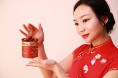 Christmas gift woman. Chinese traditional dress cheongsam holding present isolated on white background. girl in winter sweater showing gift wearing Santa hat Stock Photos