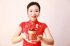 Christmas gift woman. Chinese traditional dress cheongsam holding present  on white background. girl in winter sweater showing gift wearing Santa hat. Cute Royalty Free Stock Images