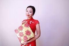 Christmas gift woman. Chinese traditional dress cheongsam holding present  on white background. girl in winter sweater showing gift wearing Santa hat. Cute Stock Photo