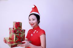 Christmas gift woman. Chinese traditional dress cheongsam holding present isolated on white background. girl in winter sweater showing gift wearing Santa hat Stock Photography