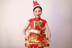 Christmas gift woman. Chinese traditional dress cheongsam holding present isolated on white background. girl in winter sweater showing gift wearing Santa hat Royalty Free Stock Image