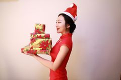 Christmas gift woman. Chinese traditional dress cheongsam holding present isolated on white background. girl in winter sweater showing gift wearing Santa hat Royalty Free Stock Photography