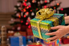 Christmas gift in woman hand - decorated tree in background. Christmas gift in woman hand closeup - decorated tree with more presents in background Royalty Free Stock Photo
