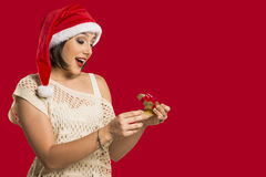 Christmas Gift - woman opening gift surprised and happy, Young b. Eautiful smiling woman in Santa hat. Funny cute photo of Brazilian / Brazilian woman over red Stock Photos