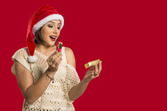 Christmas Gift - woman opening gift surprised and happy, Young b. Eautiful smiling woman in Santa hat. Funny cute photo of Brazilian / Brazilian woman over red Stock Images