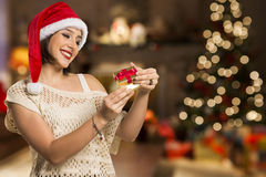 Christmas Gift - woman opening gift surprised and happy, Young b. Eautiful smiling woman in Santa hat. Funny cute photo of Brazilian / Brazilian woman over Stock Image