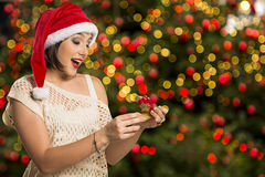 Christmas Gift - woman opening gift surprised and happy, Young b. Eautiful smiling woman in Santa hat. Funny cute photo of Brazilian / Brazilian woman over Royalty Free Stock Images