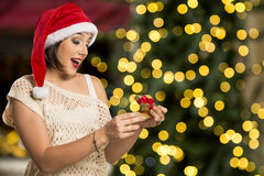 Christmas Gift - woman opening gift surprised and happy, Young b. Eautiful smiling woman in Santa hat. Funny cute photo of Brazilian / Brazilian woman over Royalty Free Stock Photo