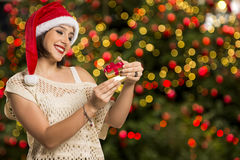 Christmas Gift - woman opening gift surprised and happy, Young b. Eautiful smiling woman in Santa hat. Funny cute photo of Brazilian / Brazilian woman over Stock Photography