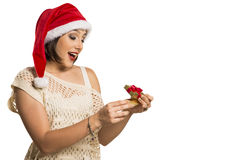 Christmas Gift - woman opening gift surprised and happy, Young b. Eautiful smiling woman in Santa hat. Funny cute photo of Brazilian / Brazilian woman in white Royalty Free Stock Photos