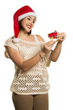 Christmas Gift - woman opening gift surprised and happy, Young b. Eautiful smiling woman in Santa hat. Funny cute photo of Brazilian / Brazilian woman in white Royalty Free Stock Photo