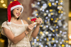 Christmas Gift - woman opening gift surprised and happy, Young b Stock Photo