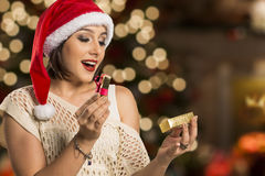 Christmas Gift - woman opening gift surprised and happy, Young b. Eautiful smiling woman in Santa hat. Funny cute photo of Brazilian / Brazilian woman over Royalty Free Stock Photography
