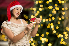 Christmas Gift - woman opening gift surprised and happy, Young b. Eautiful smiling woman in Santa hat. Funny cute photo of Brazilian / Brazilian woman over Royalty Free Stock Image