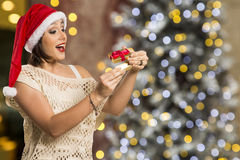Christmas Gift - woman opening gift surprised and happy, Young b. Eautiful smiling woman in Santa hat. Funny cute photo of Brazilian / Brazilian woman over Stock Photo