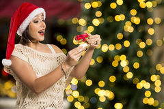 Christmas Gift - woman opening gift surprised and happy, Young b. Eautiful smiling woman in Santa hat. Funny cute photo of Brazilian / Brazilian woman over Royalty Free Stock Photos