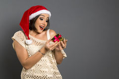 Christmas Gift - woman opening gift surprised and happy, Young b. Eautiful smiling woman in Santa hat. Funny cute photo of Brazilian / Brazilian woman over grey Stock Photo