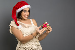Christmas Gift - woman opening gift surprised and happy, Young b. Eautiful smiling woman in Santa hat. Funny cute photo of Brazilian / Brazilian woman over grey Stock Images