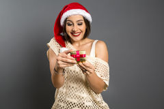 Christmas Gift - woman opening gift surprised and happy, Young b. Eautiful smiling woman in Santa hat. Funny cute photo of Brazilian / Brazilian woman over grey Royalty Free Stock Images