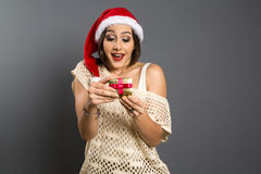 Christmas Gift - woman opening gift surprised and happy, Young b. Eautiful smiling woman in Santa hat. Funny cute photo of Brazilian / Brazilian woman over grey Royalty Free Stock Photos