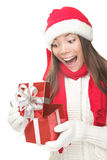 Christmas gift woman opening present surprised. Christmas Gift - woman opening gift surprised and happy, Young beautiful smiling woman in Santa hat. Funny cute Stock Photography