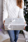 Christmas Gift. woman showing beautiful gift box. Closeup of present on christmas background Royalty Free Stock Photo