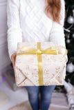 Christmas Gift. woman showing beautiful gift box. Closeup of present on christmas background Stock Photo